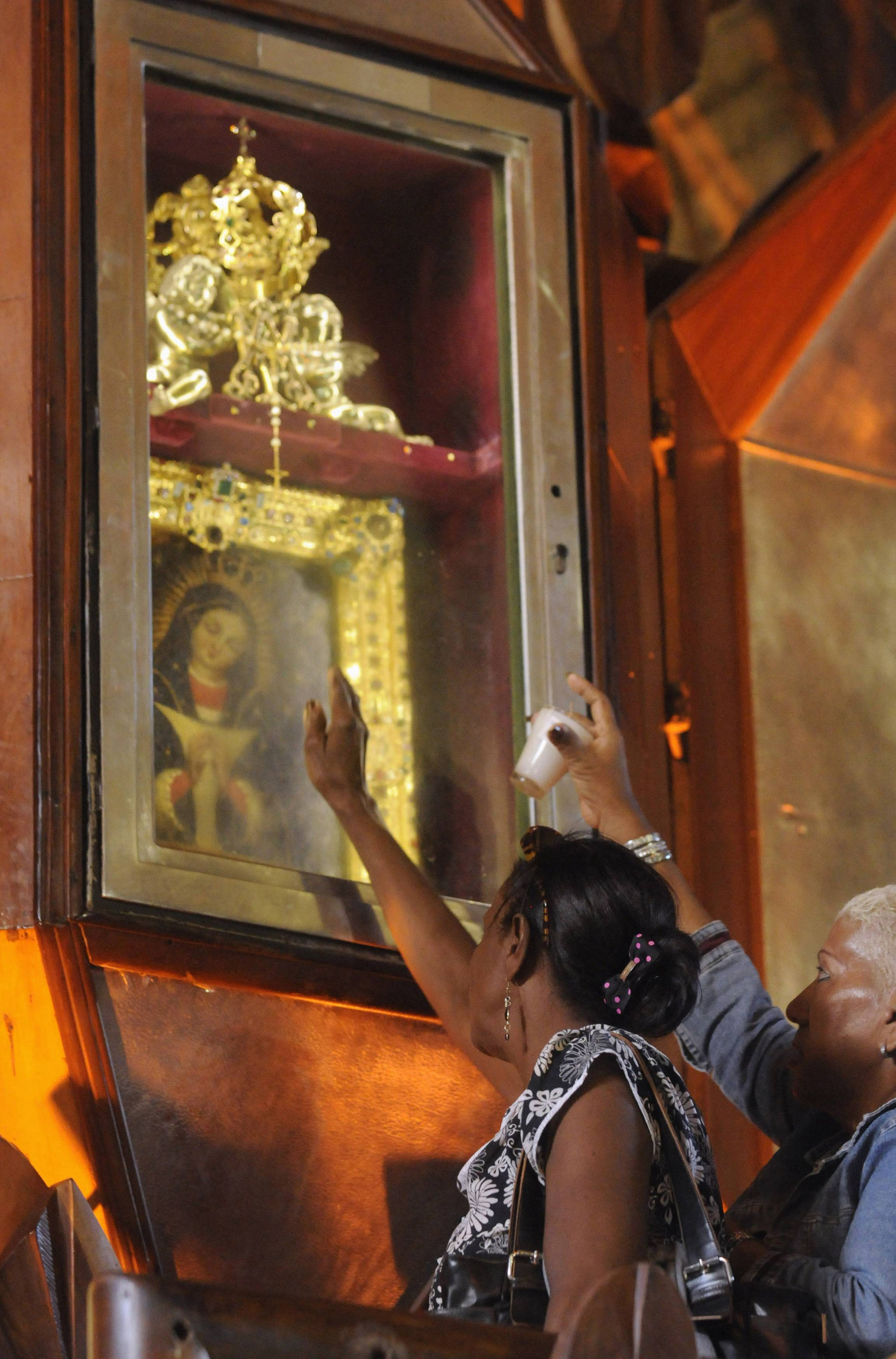 Women pray in front of an image of Mary Jan. 20, 2013 the eve of the feast of Our Lady of Altagracia at the basilica in Santo Domingo, Dominican Republic.