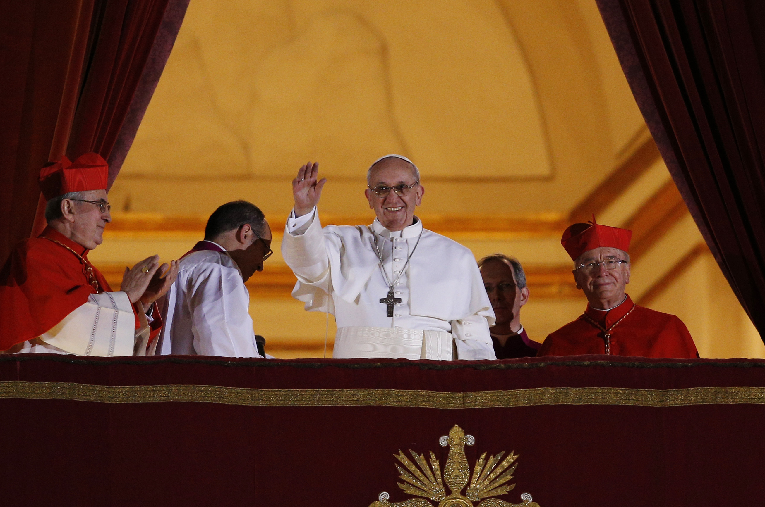 Pope Francis waves from the central balcony of St. Peter's Basilica following his election March 13, 2013.