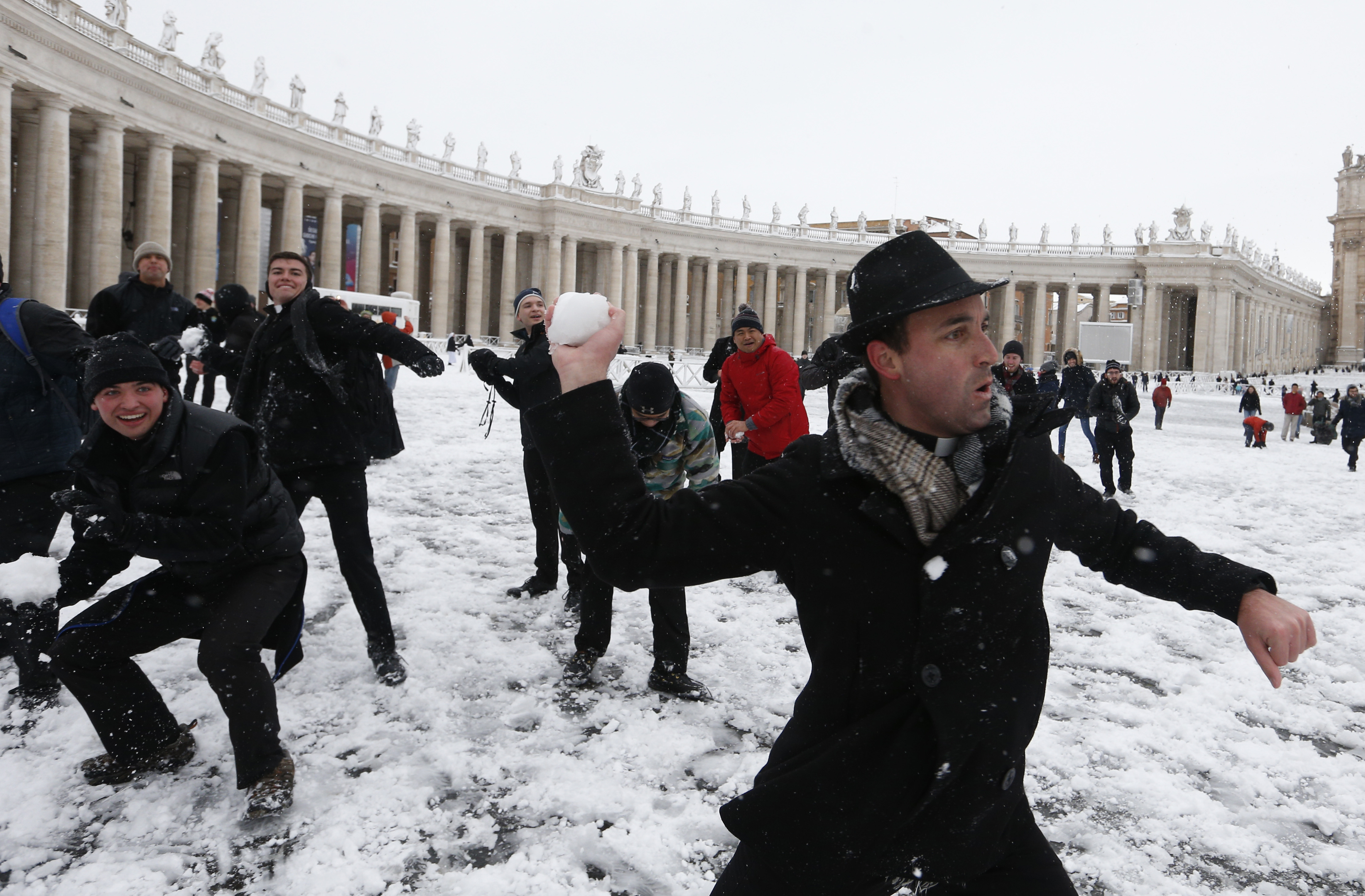 Father Robert Kilner, right, and seminarians from the Pontifical North American college engage in a snowball fight with their peers from the Venerable English College in St. Peter's Square at the Vatican after a rare snowfall Feb. 26. (CNS photo/Paul Haring)