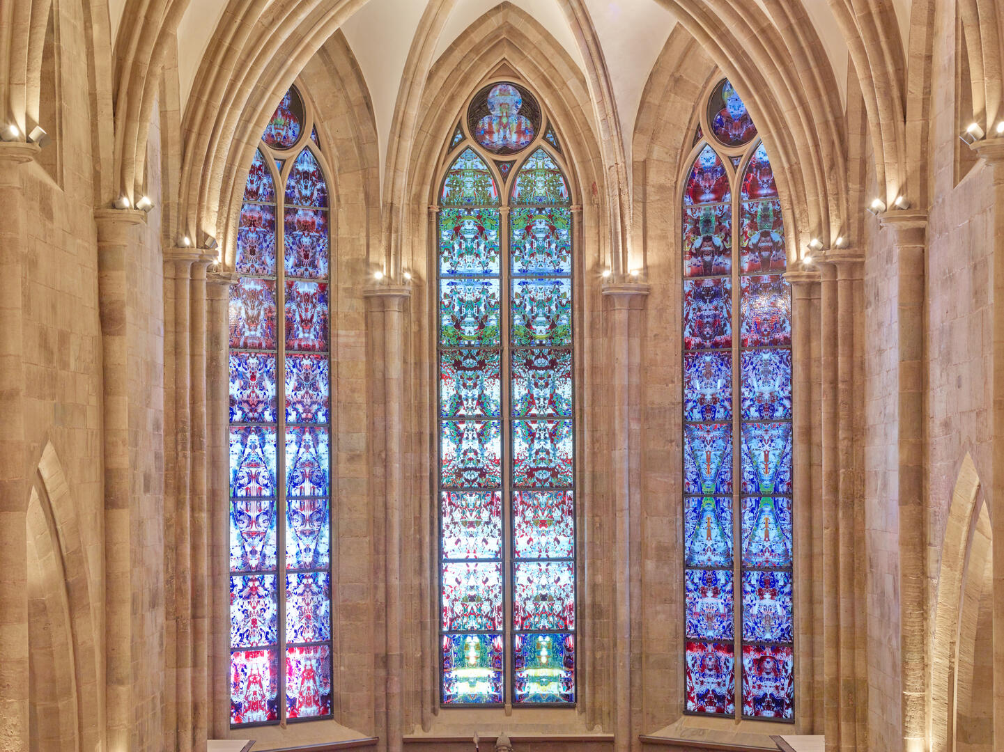 The three Richter choir windows at Tholey Abbey, with designs like a Persian rug or kaleidescope; the far left window mostly pinks, blues and purples; the middle of greens, reds and blues; the right of similar coloring to the left, but deeper hues, and bits of green