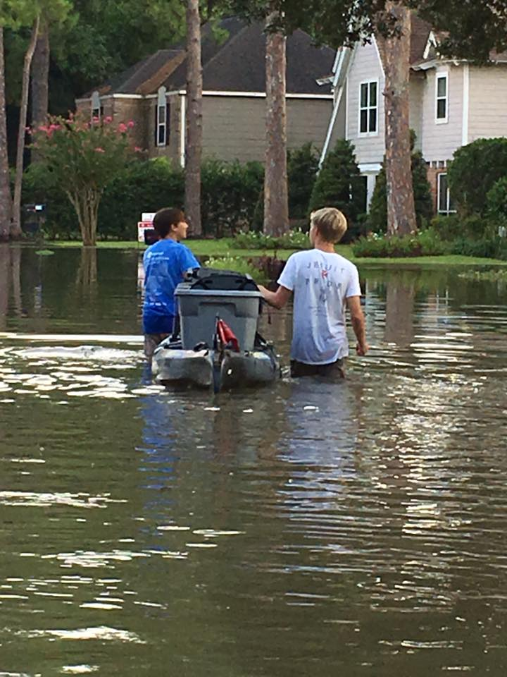 Two Strake Jesuit students guide a kayak full of belongings through Hurricane Harvey floodwaters. (Photo by Sharon Lundrigen)
