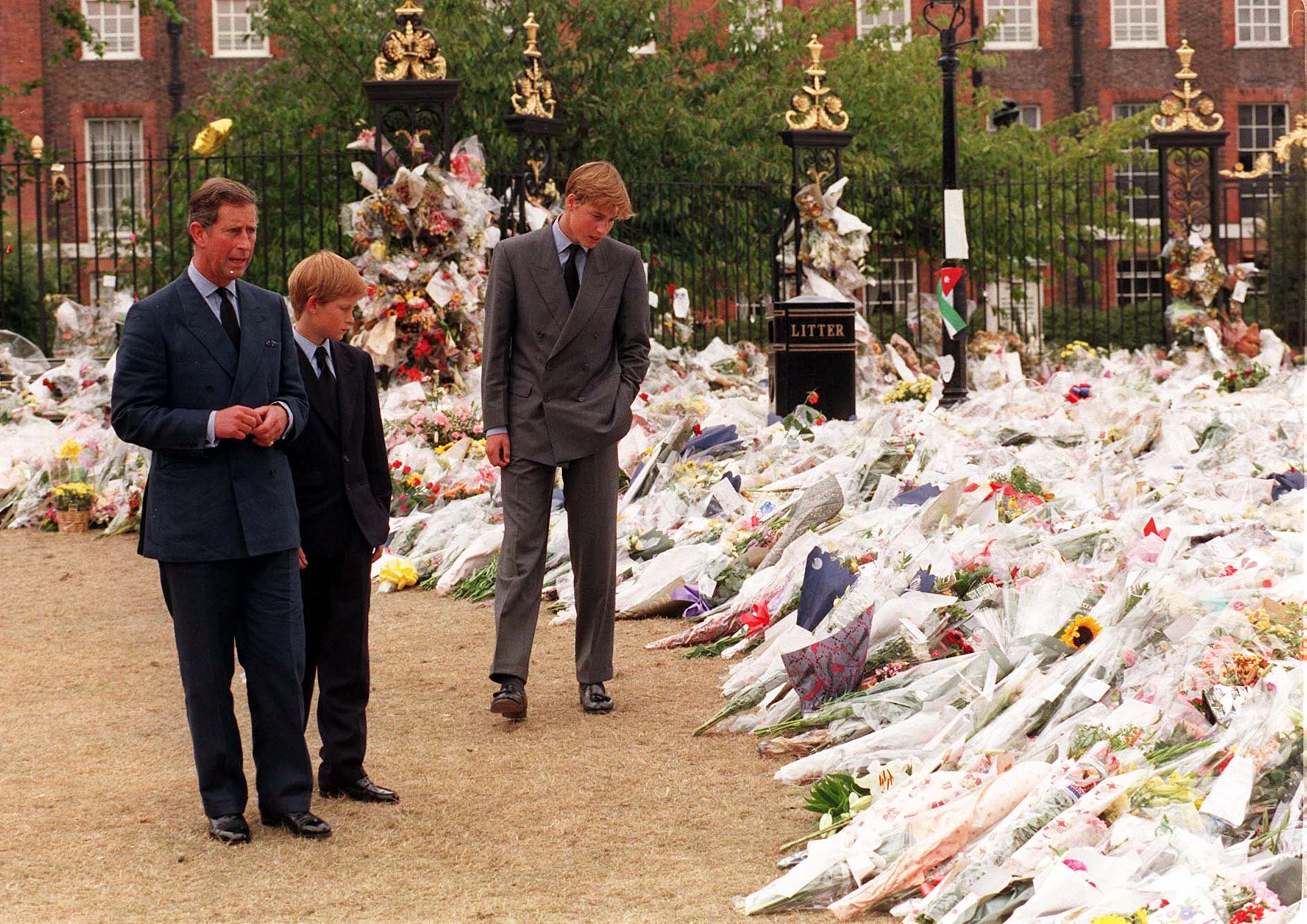 File photo dated 5/9/1997 of the Prince of Wales and his sons Prince William (right) and Prince Harry, view the sea of floral tributes to Diana, Princess of Wales, at Kensington Palace. The Princes on Wednesday viewed tributes attached to the Golden Gates of the Palace in London ahead of the 20th anniversary of their mother's death. Issue date: Friday September 5, 1997.