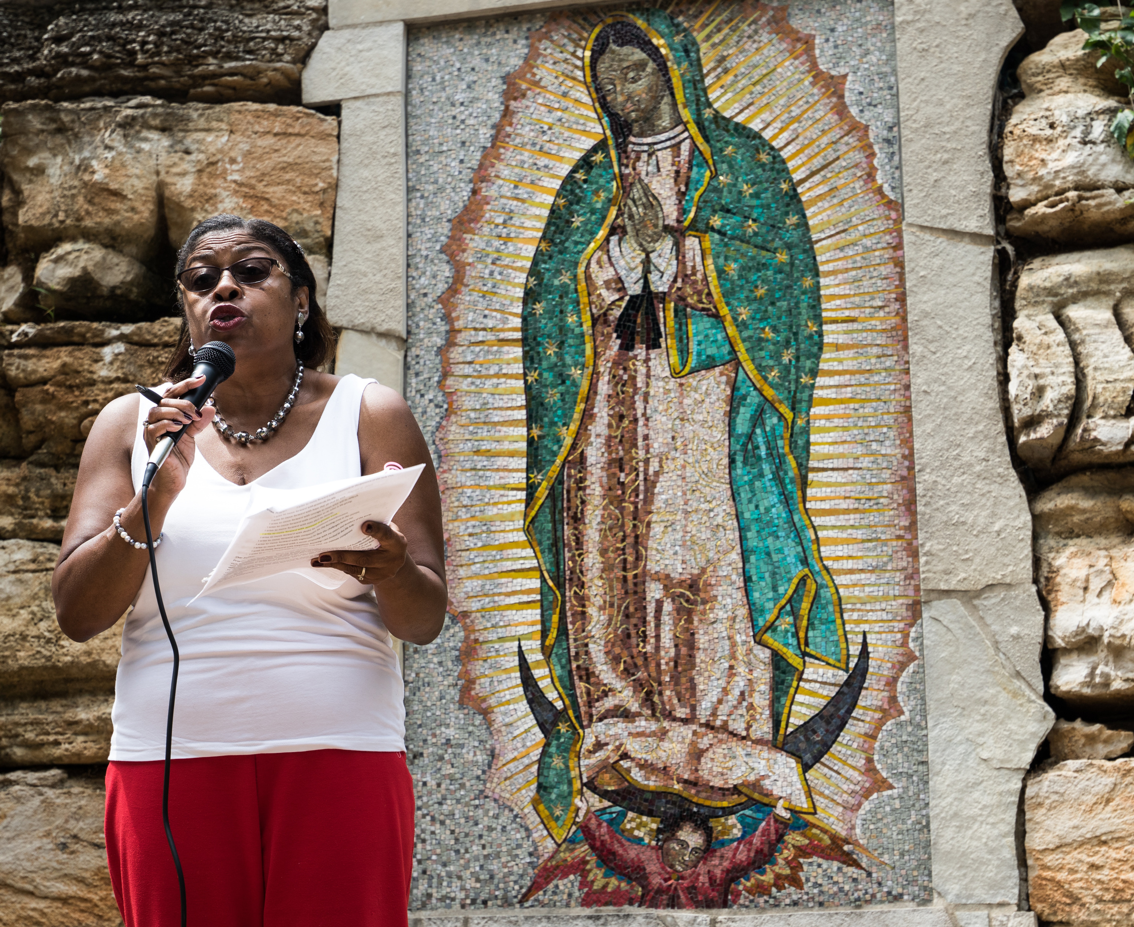 A woman speaks during an Aug. 5 ecumenical prayer service at grotto at Our Lady of Guadalupe Church in Ferguson, Mo. The service commemorated the first anniversary of the shooting death of 18-year-old Michael Brown. (CNS photo/Weston Kenney, St. Louis Review)