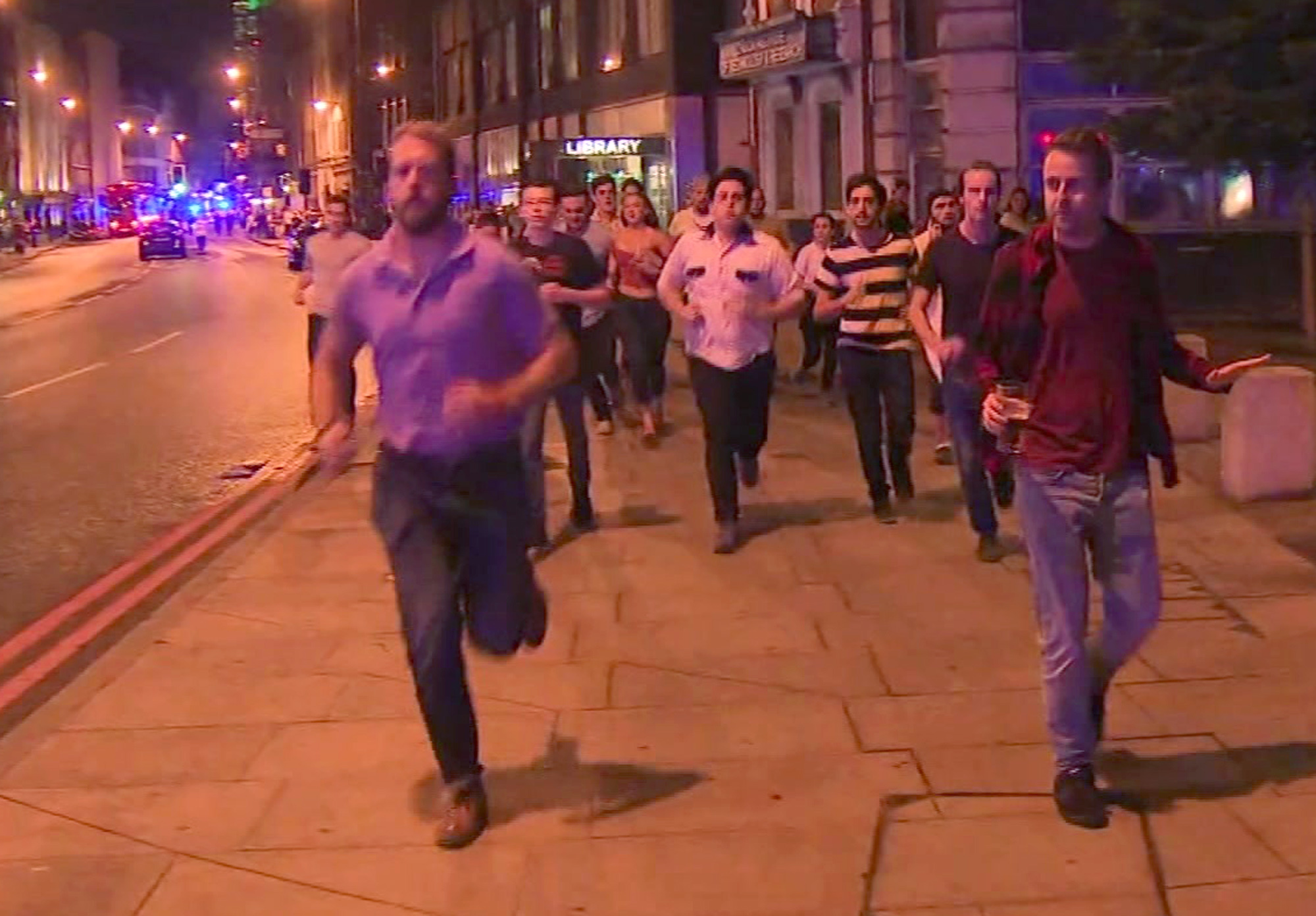 In this image taken from video footage, people run from the scene of attack, alongside a man strolling holding a pint of beer in London on June 3. (Sky news via AP)