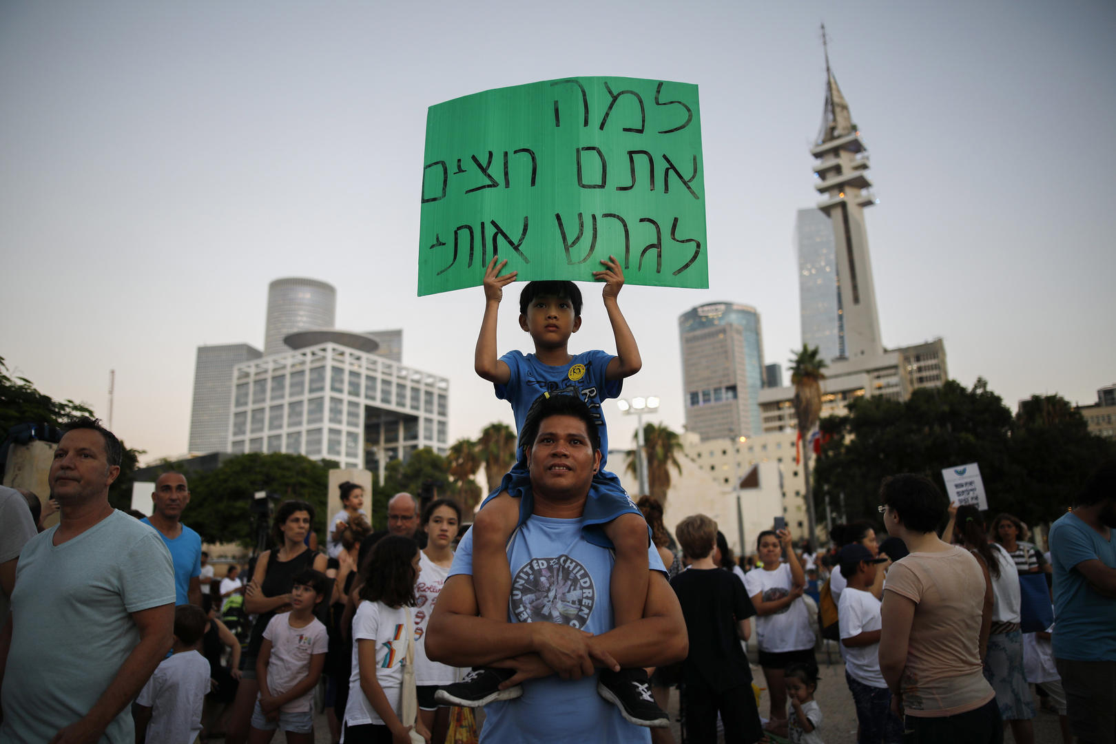 "Image: A child holds a sign that reads, ""Why do you want to deport me?"" during a protest in Tel Aviv on Aug. 6. (Photo: Corinna Kern)"