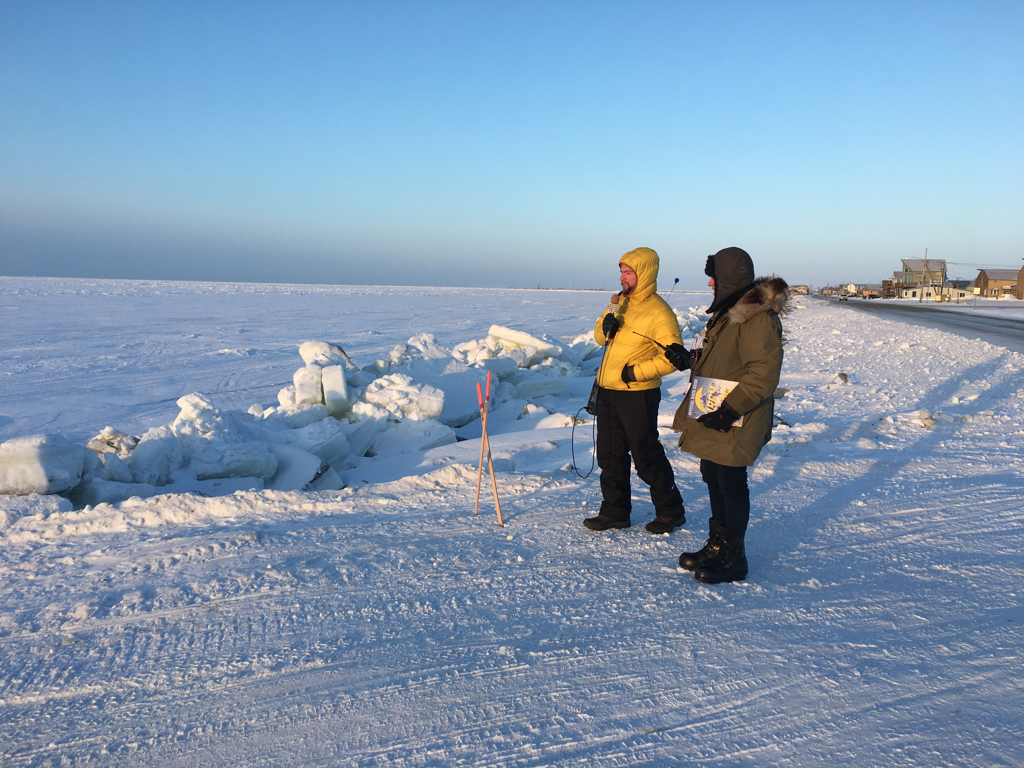 Davis Hovey and fellow reporter Tyler Stup await the arrival of the Iron Dog Snowmachine racers on the frozen Bering Sea.