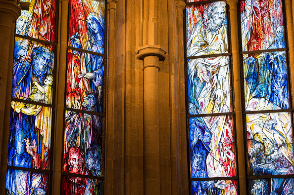 Two windows in Tholey Abbey; On the left, a Christmas image of Joseph holding baby Jesus near Mary in reds, blues and yellows; on the right, a Pentecost image of Jesus in white and yellow, the disciples in red and blue