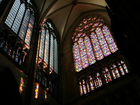 Light comes through Gerhard Richter's window in Cologne Cathedral, comprised of squares of 72 different colors; the light falls onto a wall on the left side, painting the wall in pillars of rainbow light