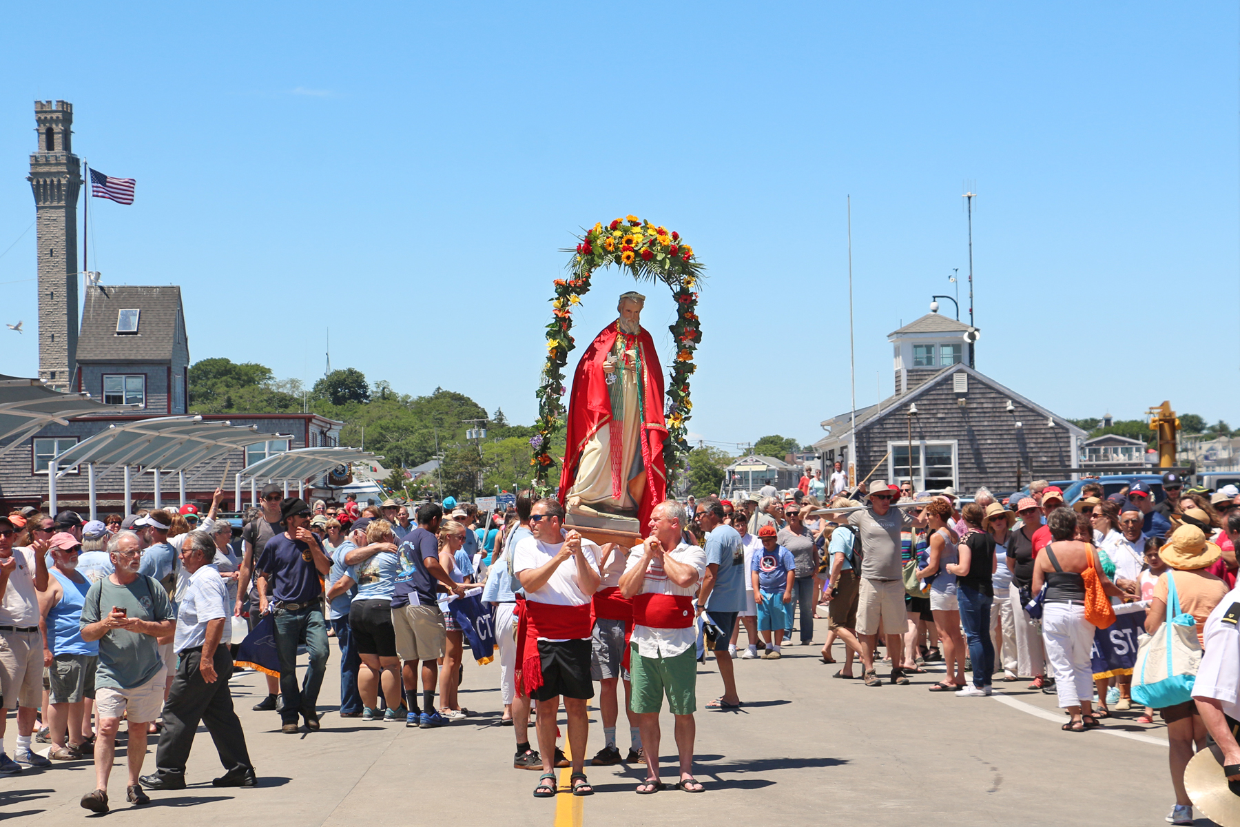 A statue of Saint Peter sporting the colors of the Portuguese flag is carried onto MacMillian Pier. In the background to the left stands the Pilgrim Monument, built in 1910 to commemorate the 1620 signing of the Mayflower Compact in Provincetown.