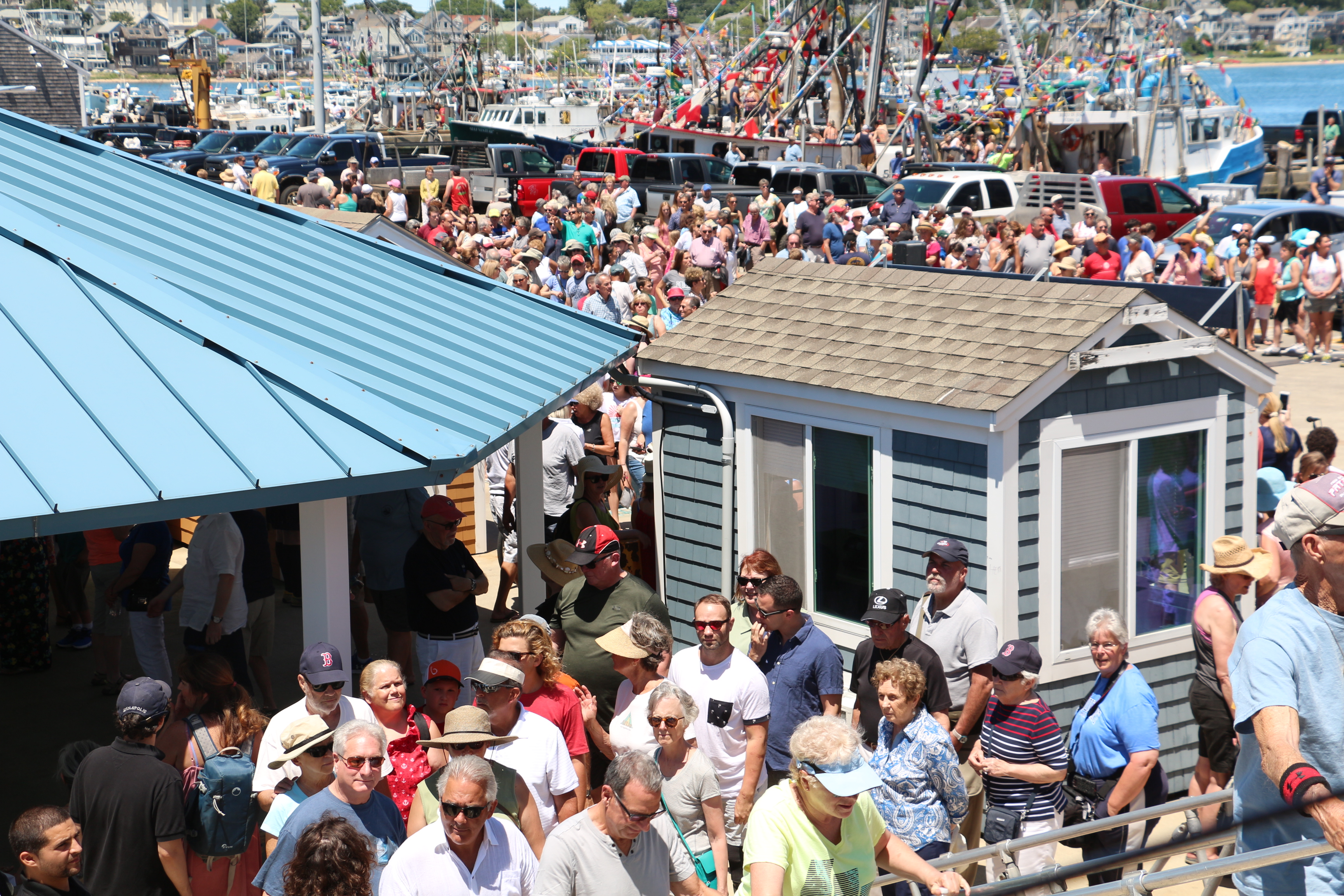 Crowds line up to board the ferry on which the bishop will stand to bless the fishing fleet.