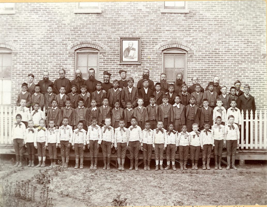 Jesuit and Lakota students pose for a photo outside the Holy Rosary Mission.
