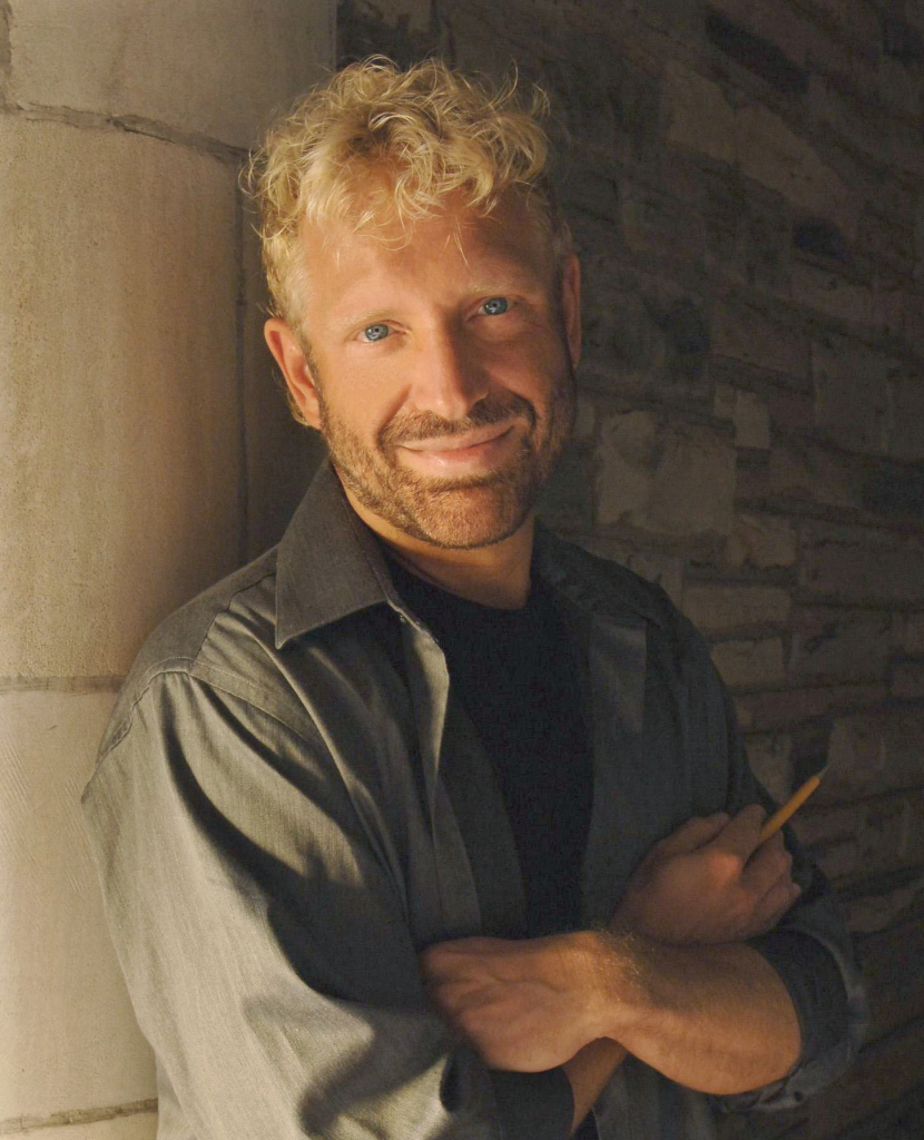 the composer Michael Kurek stands with a pencil in his hand; he is strawberry blonde with bright blue eyes and a darker blonde beard