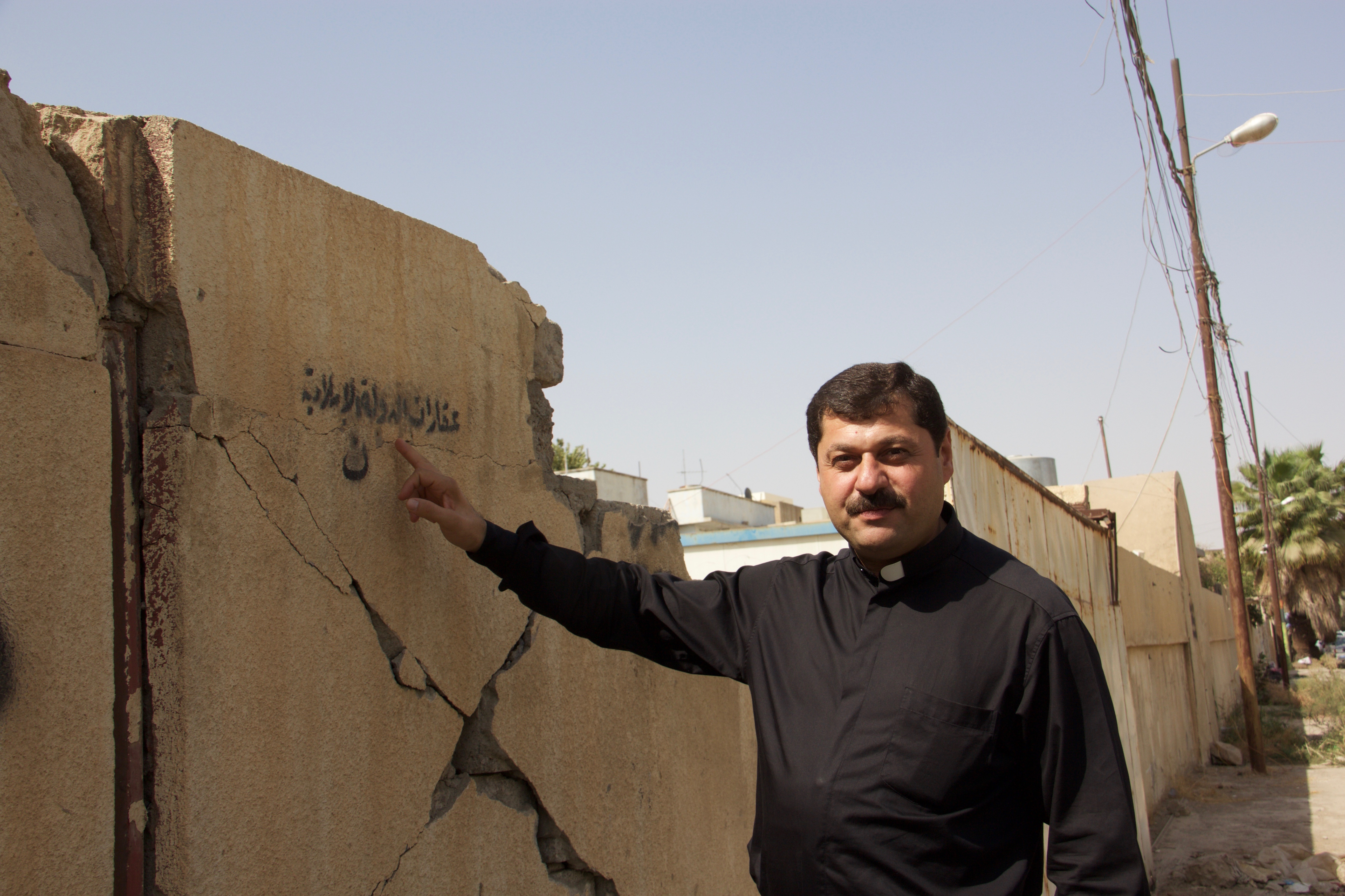 """Image: Father Emanuel Adel Kloo, a Syriac Catholic priest, points to now-outdated graffiti left by Daesh: """"Christians, this property belongs to the Islamic State."""" (Kevin Clarke)"""