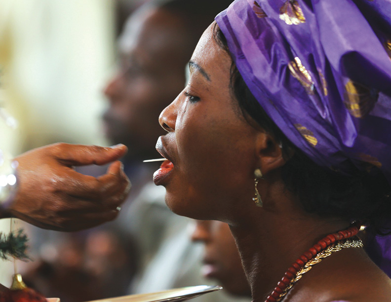 A woman receives communion during a New Year's day service at the Holy Rosary Catholic Church in Abuja, January 1, 2014. REUTERS/Afolabi Sotunde