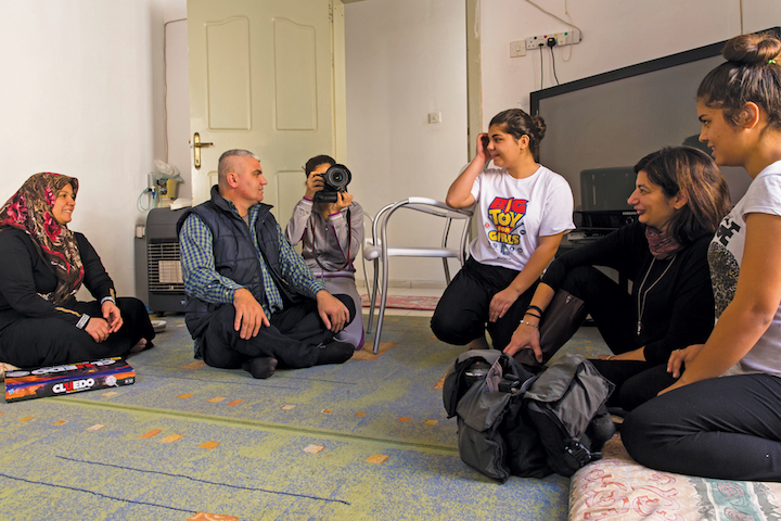 Refugees sit with Katrine Camilleri of Jesuit Refugee Service Malta