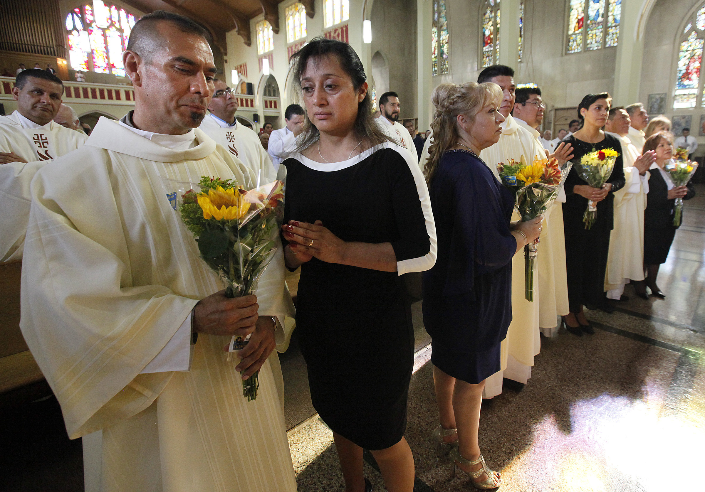 Benito Gallegos presents flowers to his wife, Martha, after his ordination  as a deacon May 29. Chicago Archbishop Blase J. Cupich ordained five  Hispanic men ...