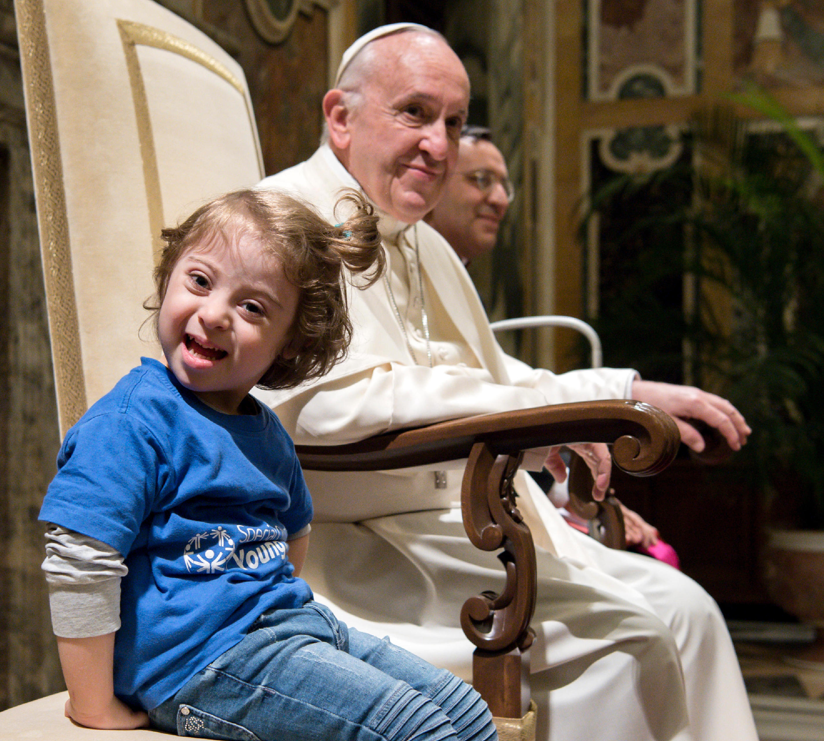32324d4b3731 A young girl sitting next to Pope Francis smiles during an audience with  Special Olympics athletes