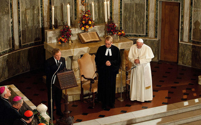 Pope Francis is flanked by Rev. Jens-Martin Kruse, during a visit to Christuskirche, a parish of the German Evangelical Lutheran Church, in Rome in this Nov. 15, 2015, file photo.