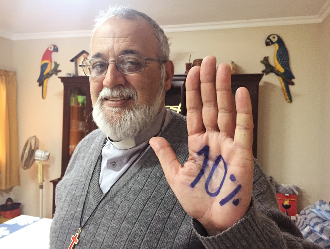 "Camillian Father Mateo Bautista Garcia shows his hand with ""10%"" written on it. The priest wants Bolivia's government to spend 10 percent of its budget on health care. (CNS photo/David Agren)"