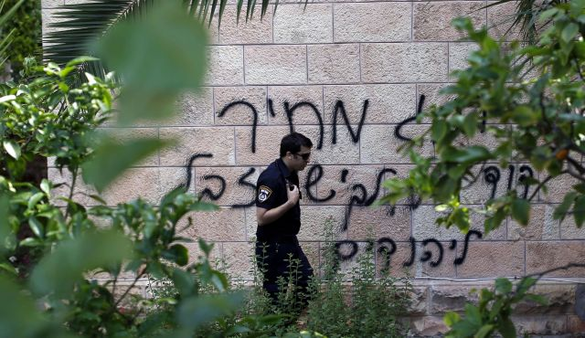 "Graffito on a church in Jerusalem: ""King David is for the Jews, Jesus is garbage."" (Photo by AFP)"