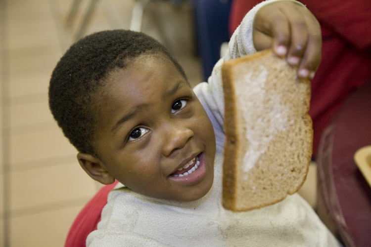Three-year-old Matthew Malone shows off part of his lunch at the Capuchin Soup Kitchen in Detroit Nov. 13. (CNS photo/Jim West)