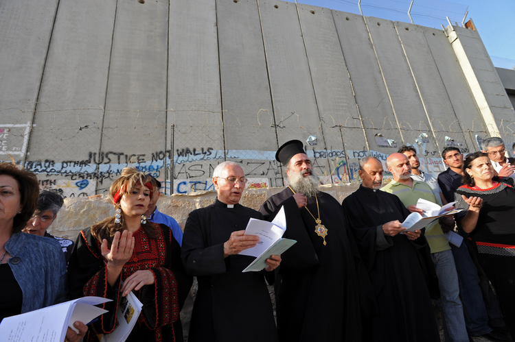 Christian leaders pray in front of the Israeli separation wall near Rachel's Tomb in Bethlehem, West Bank, May 29, the beginning of the 2010 World Week for Peace in Palestine and Israel. (CNS photo/Debbie Hill)