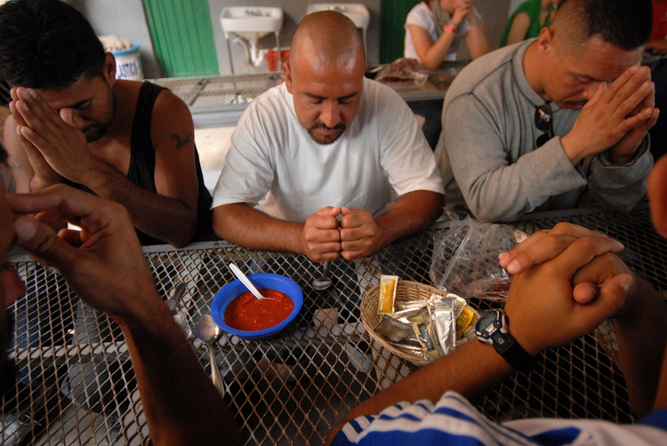 Migrants pray before breakfast at a dining facility in Nogales, Mexico, that is supported by the Jesuit-run Kino Border Initiative. (CNS photo/David Maung)