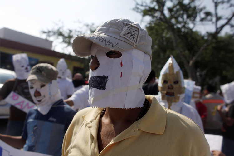 Migrants from Guatemala and El Salvador cover their faces with paper masks Aug. 28 before a silent march in Saltillo , Mexico, in honor of the 72 migrants who were killed Aug. 24, 2010, in the Mexican state of Coahuila.