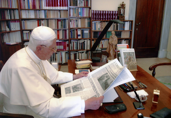 Pope Benedict XVI reading the Vatican's L'Osservatore Romano newspaper (CNS photo/L'Osservatore Romano via Catholic Press Photos)