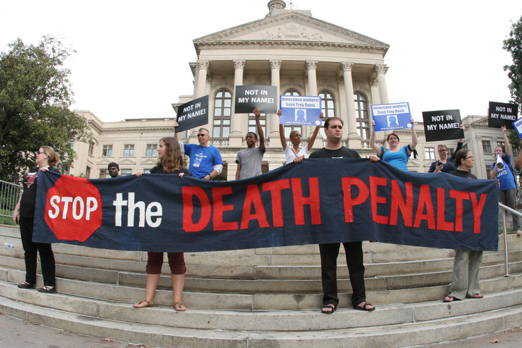 People hold a banner and signs on the steps of the Georgia Capitol in Atlanta during a vigil for death-row inmate Troy Davis before his Sept. 21 execution. (CNS photo/Michael Alexander, Georgia Bulletin)