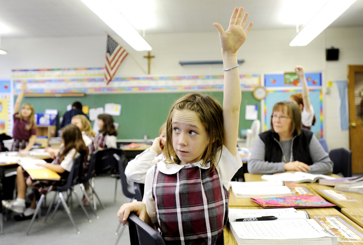 Fourth-grader Shannon Lawless raises her hand to answer a question Dec. 20, 2011, at Christ the King School in Irondequoit, N.Y. (CNS photo/Mike Crupi, Catholic Courier)