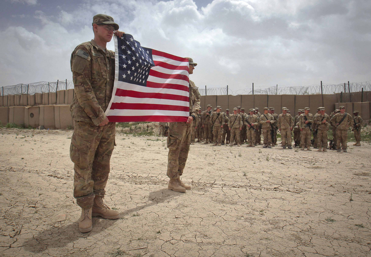 U.S. soldier hold American flag during Memorial Day ceremony in Afghanistan. (CNS photo/Danish Siddiqui, Reuters)