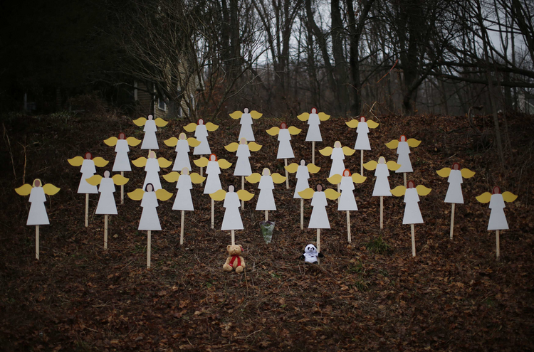 Twenty-seven wooden painted angels created by Eric Mueller are displayed outside his home in Newtown, Conn. (CNS photos/Mike Segar, Reuters).