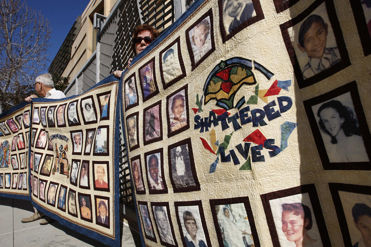 In this 2013 file photo, people stand outside the Cathedral of Our Lady of the Angels holding quilts bearing photos of victims of sexual abuse by priests of the Los Angeles Archdiocese. (CNS photo/David McNew, Reuters)