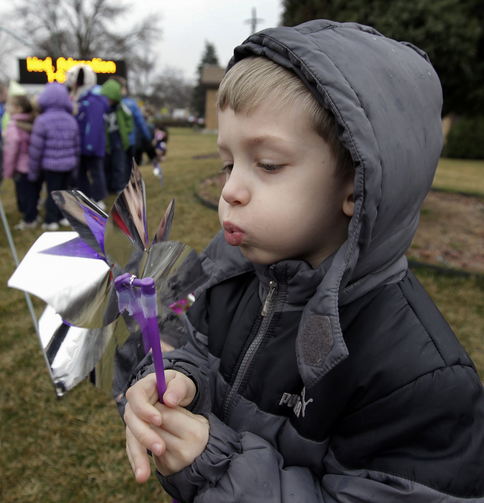 Pre-K student Patrick Meade plays with a pinwheel April 9 as students of St. Thecla School in Chicago mark National Child Abuse Prevention Month.