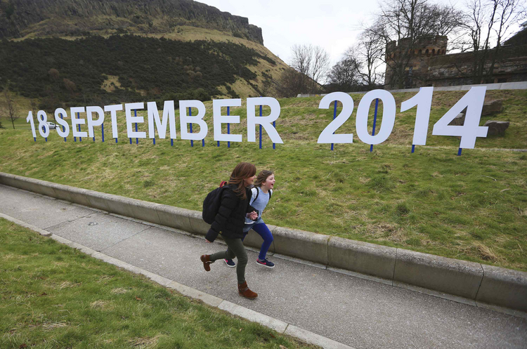 Teacher and schoolgirl run in front of sign indicating date of Scotland's independence referendum. (CNS photo/David Moir, Reuters)