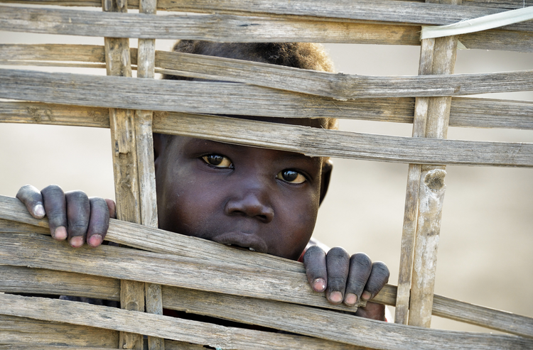 Boy displaced by conflict peers through fence in contested Sudanese border region. (CNS photo/Paul Jeffrey)