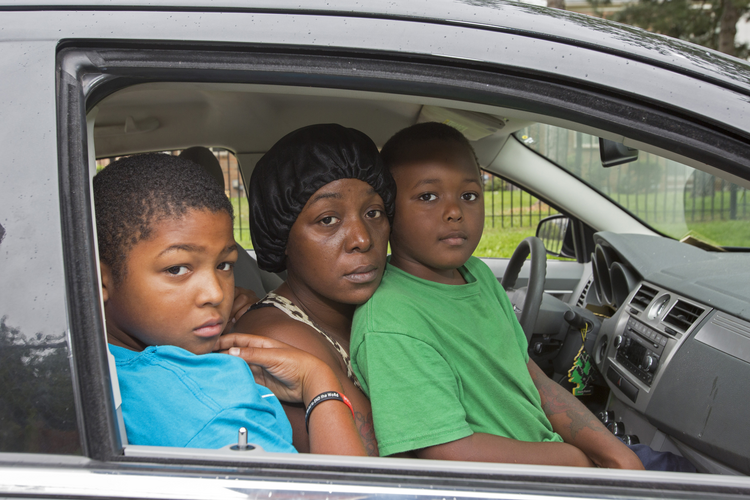 Homeless family living out of car pose for photo in Detroit. (CNS photo/Jim West)
