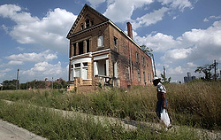 Man walks past a vacant home in Detroit neighborhood (CNS photo)