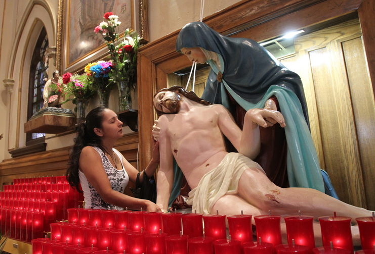 A woman touches a statue of Jesus and Mary as she prays at Our Lady of Sorrows Church in the Corona neighborhood of the New York borough of Queens. (CNS photo/ Gregory A. Shemitz)