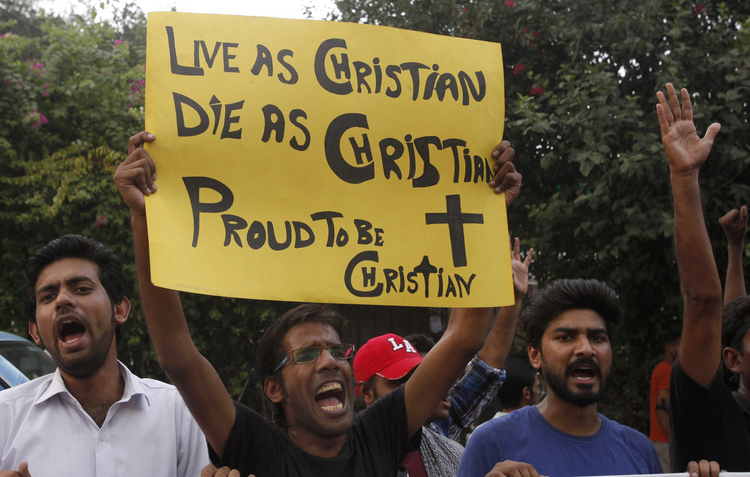 Member of Christian community holds placard during rally to condemn suicide attack on church in Pakistan.
