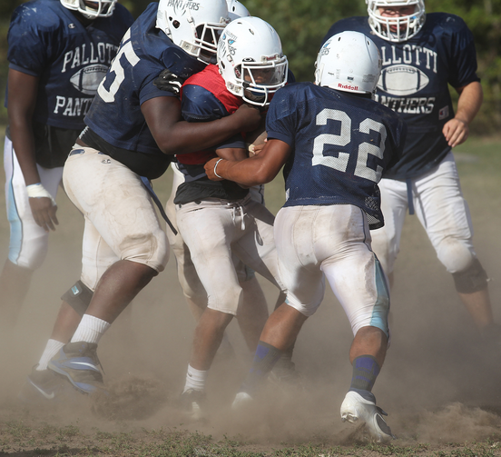 Players converge on quarterback during football practice at Maryland Catholic high school. (CNS photo /Bob Roller)
