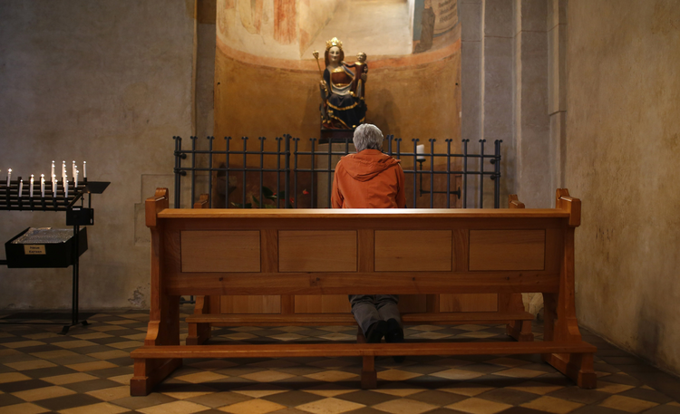 Woman kneels in prayer inside Limburg Cathedral (CNS photo/Kai Pfaffenbach, Reuters)
