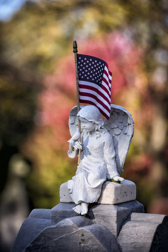 American flag sits on gravestone topped by angel figure at Wisconsin cemetery. (CNS photo/Sam Lucero, The Compass)