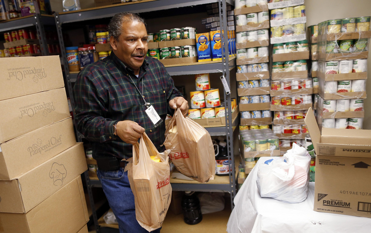 Volunteer carries bags of food for Emergency Assistance Department at Chicago Catholic Charities (CNS photo/Jim Young, Reuters)