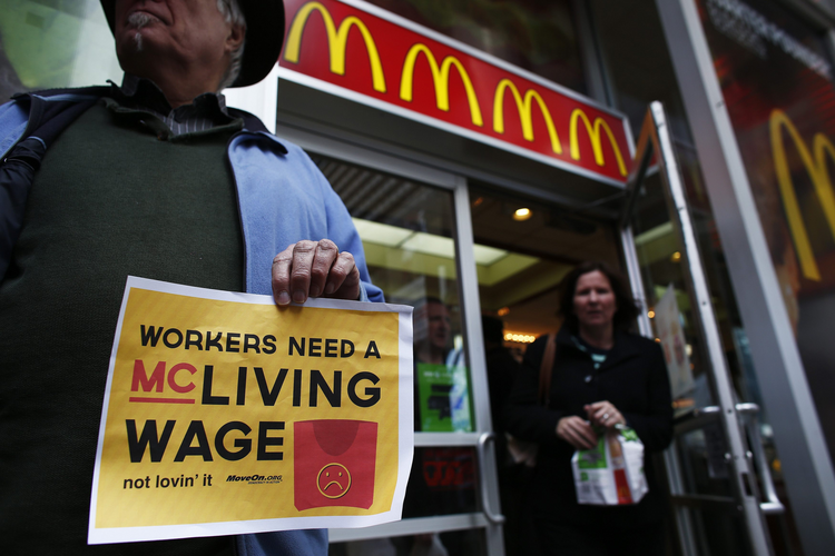 Woman exits McDonald's while fast-food workers protest for higher wages in New York (CNS photo/Eduardo Munoz, Reuters)