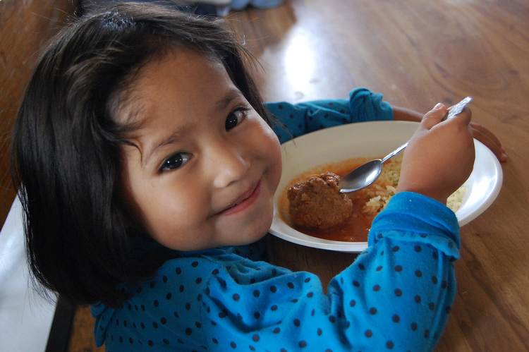 Girl eats meal provided by charity, local Caritas program in Mexico.