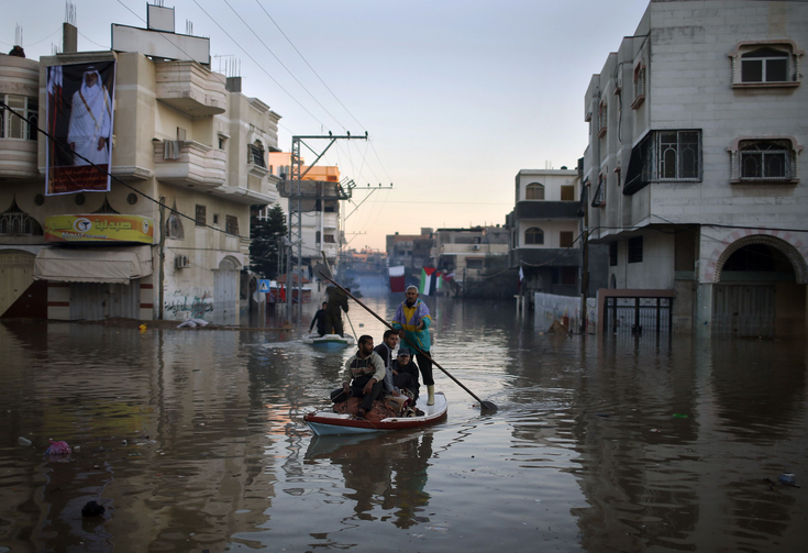 Palestinian civil defense volunteers paddle boat to evacuate people after flooding in Gaza Strip. (CNS photo/Mohammed Salem, Reuters)