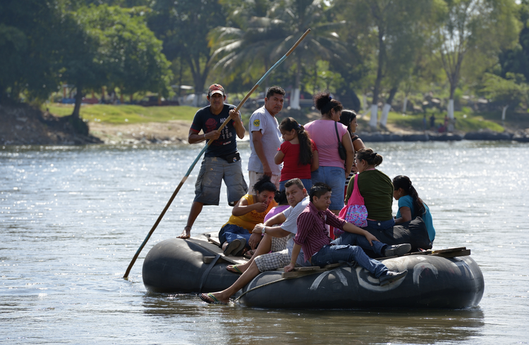 Migrants and others cross the Suchiate River where it forms a border between Guatemala and Mexico Dec. 18. The river crossing is part of the main route that Central American migrants follow on their way north. (CNS photo/Paul Jeffrey)