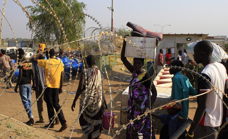 People walk past razor wire Jan. 7 at Tomping camp, where thousands of displaced people who fled their homes are sheltered by the United Nations near Juba, South Sudan. (CNS photo/James Akena, Reuters)
